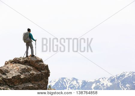 successful woman backpacker hiking on mountain peak cliff