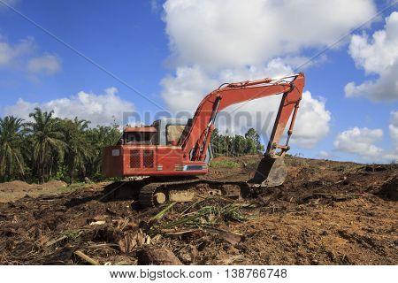 Deforestation environmental problem excavator destroying rainforest trees, Borneo