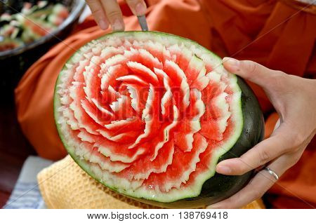 crafts carved watermelon with the hand and carving knife
