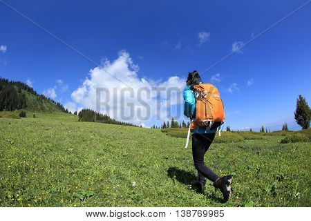young woman backpacker hiking on beautiful mountain peak trail