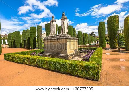 The scenic gardens of the Alcazar de los Reyes Cristianos with statues of the Catholic Monarchs Ferdinand and Isabella and Christopher Columbus. Cordoba, Andalusia, Spain.