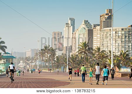 DURBAN SOUTH AFRICA - APRIL 16 2016: Locals and Tourists enjoying the Golden Mile Promenade just after sunrise.