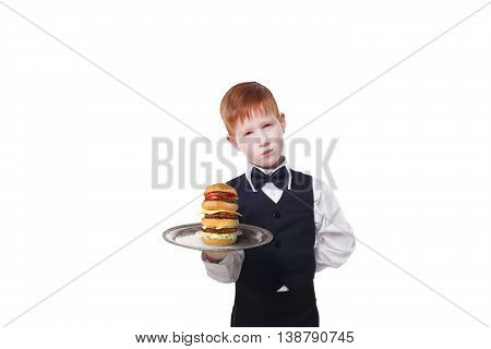 Little sad and tired waiter stands with tray serving big double hamburger. Redhead child boy in suit plays hardworking restaurant servant, gives burger isolated at white background