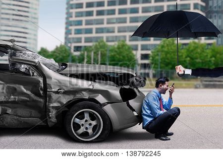 Angry man talking on the mobile phone while sitting under an umbrella after traffic accident. Insurance concept of traffic accident