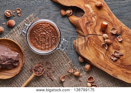 Glass jar of hazelnut spread with nuts pieces on dark wooden background