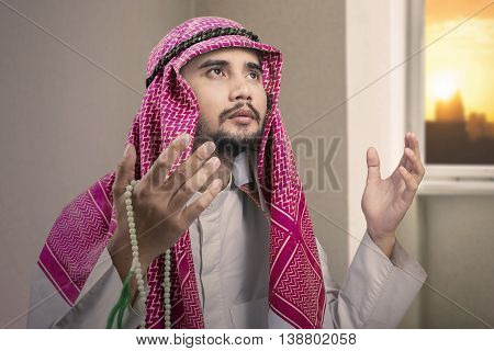 Portrait of a middle eastern man worshipping to Allah by raising his hands at home