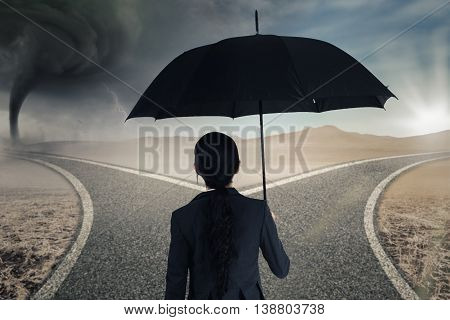 Back view of female worker holding umbrella while looking at two road with storm and bright sunlight