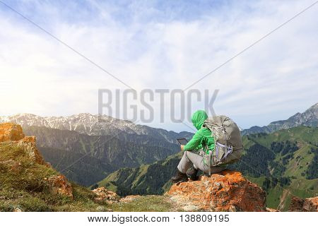 successful woman backpacker use digital tablet taking photo on mountain peak cliff