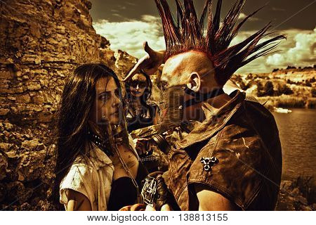 Raider with mohawk hairstyle young pretty slave in iron mask and slave trader posing over post-apocalyptic wasteland.