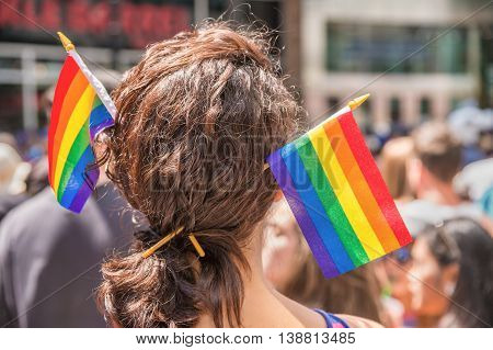A female spectator with two rainbow flag hair sticks is watching the gay pride parade in Toronto Canada.