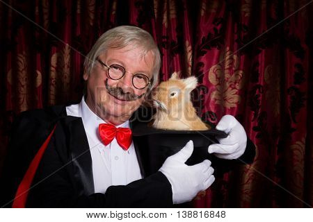 Funny illusionist on stage with a rabbit in his top hat
