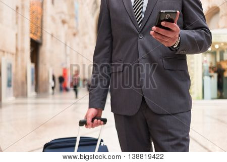 Traveler pushing his trolley while looking at his mobile phone