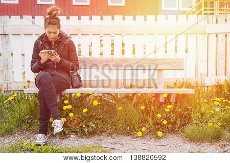 Hipster beautiful woman texting her mobile to another women in sunset between yelow flower by vintage style.