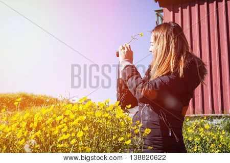 hipster beautiful woman play with her camera on flower garden. - woman with retro vintage camera on blue sky background enjoying sunset.