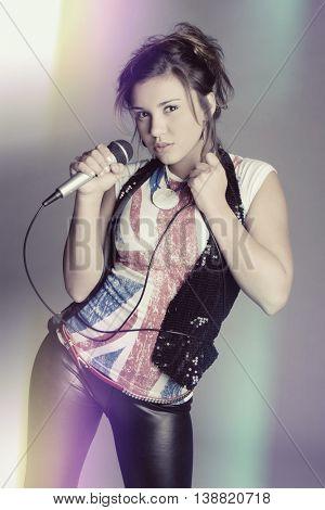 Young woman singing karaoke into microphone