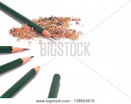 five sharpened and unsharpened green pencils with pencil sawdust