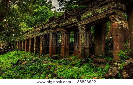 Crumbling ancient Khmer runis in the green jungle of Cambodia