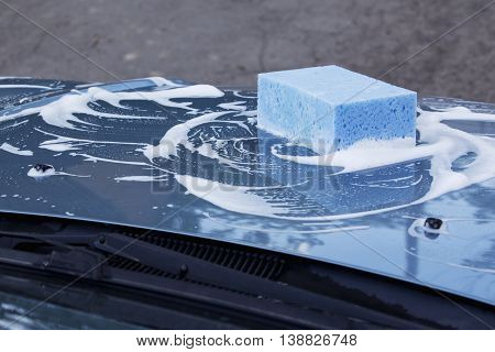a blue car is washing in soap suds