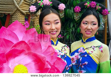 two chinese women in traditional dresses and lotus floral parasol