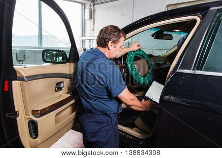 Serviceman making car diagnostics with laptop in a workshop. Automobile computer inspecting at repair shop.