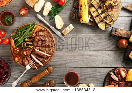 Grilled beef steak with grilled vegetables on wooden table with copy space. Top view. Outdoors Food Concept