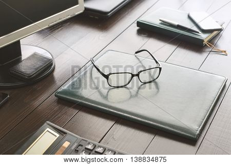 Glasses on the leather business folder on the office desktop close up