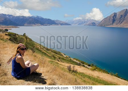 New Zealand woman enjoying the sun and beautiful lakeside view