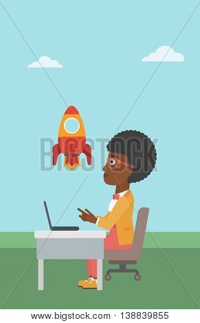 An african-american business woman sitting at the table and looking at a flying rocket. Business woman working on laptop. Business start up concept. Vector flat design illustration. Vertical layout.