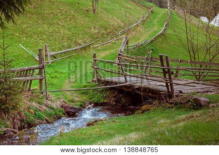 Dilapidated abandoned wooden bridge in mountain village. Deserted village