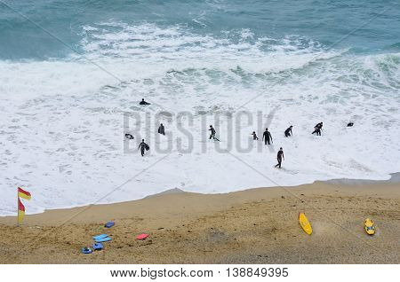Newquay Cornwall United Kingdom - July 01 2016: Looking down on group of surfers in wetsuits on beach