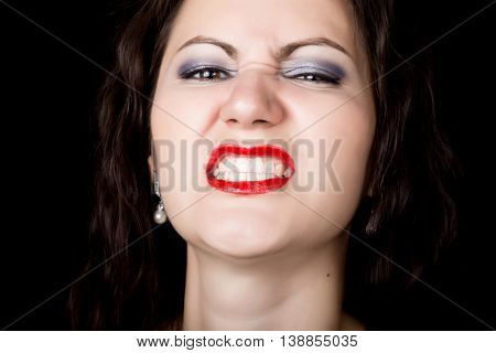 Close-up woman looks straight into the camera on a black background. expresses different emotions, showing teeth, showing grin growls.