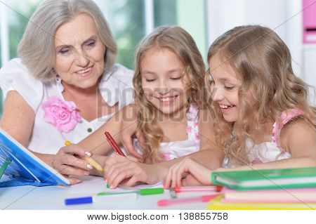 Old woman with tweenie   girls doing homework  at home