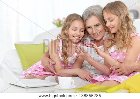 Old woman with tweenie   girls and  phone and laptop at home