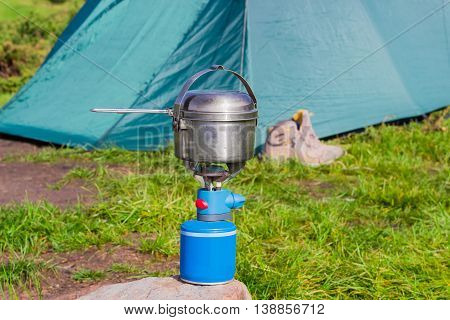 Blue gas cartridge camping stove and small stainless steel pot on a stone on a background of the tent during cooking