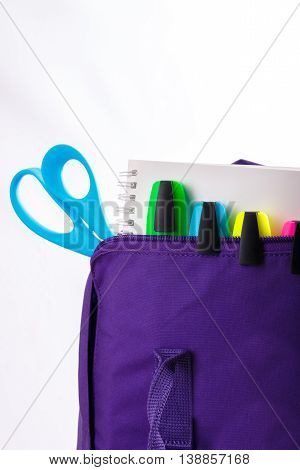 Open purple backpack with school supplies on white background. Back to school. Close up.