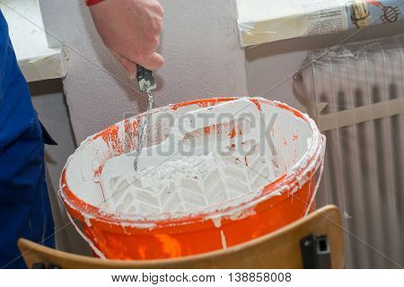 Painter and interior decorator touches paint roller to paint grid from