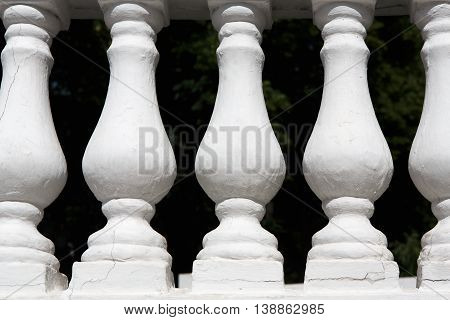 White cement balusters elements closeup at black background. Painted granite balustrade ta staircase, architectural detail.