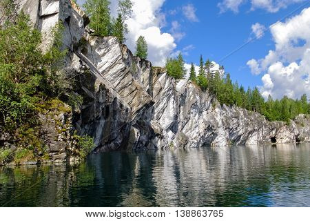 Grand and massive marble canyon. Occurrence of white and grey marbles. Stone cliff going into the water. Landscape of mountains and sky.