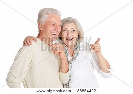 Portrait of a happy senior couple, woman poiting  at white background