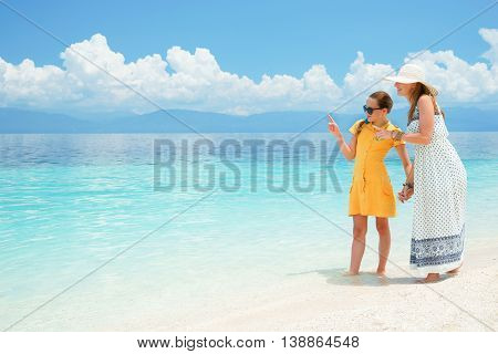 Youn europian woman in light dress is sitting on the white sand beach near beautiful tropical sea and cares about her teen daughter at sunny day under blue sky with scienic clouds.
