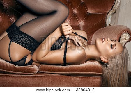 sexy woman in seductive black lingerie lying on a couch in stockings