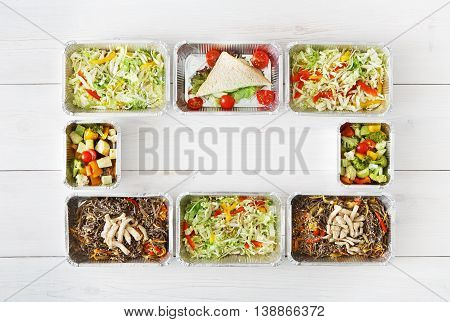 Healthy food delivery, daily ration. Take away of natural organic low carb diet. Fitness nutrition in foil boxes frame. Top view, flat lay with copy space at white wood