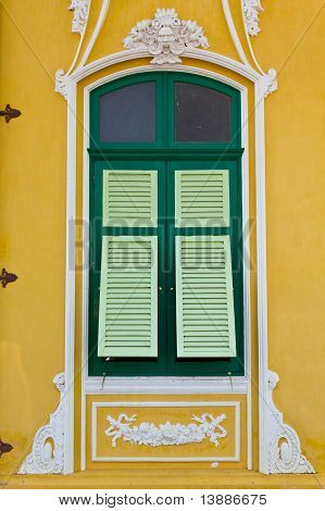 The Closed Green Window On The Yellow Wall