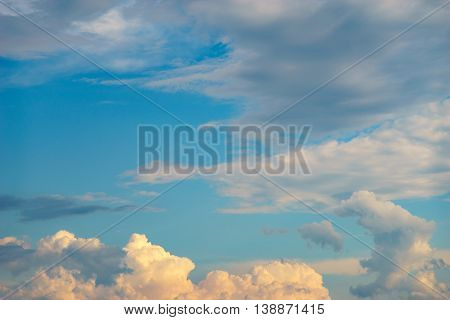 Evening sky with fluffy clouds in late afternoon sunlight