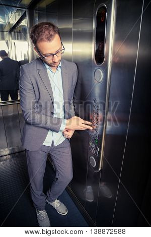 Portrait of a businessman in the elevator pressing the third floor button.
