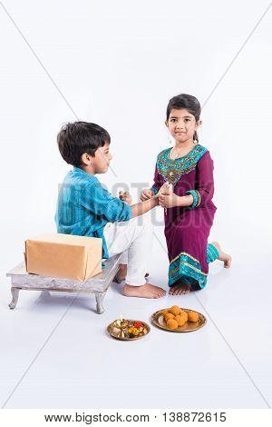 cute indian Sister tying Rakhi on her brother's wrist on the occasion of Rakshabandhan 0r raksha bandhan or Rakhi festival, isolated on white background