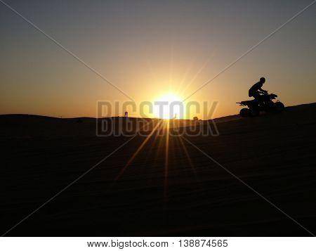 ATV in the desert at sunset background.