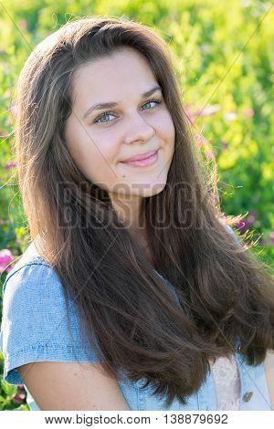Portrait of a teenager 15 years with long hair in a meadow