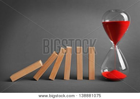 Hour glass blocked row of falling dominoes on grey background