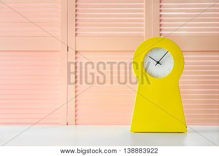 Stylish clock on pink folding screen background